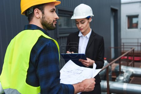 selective focus of architect and builder in helmets with blueprint and clipboard on construction