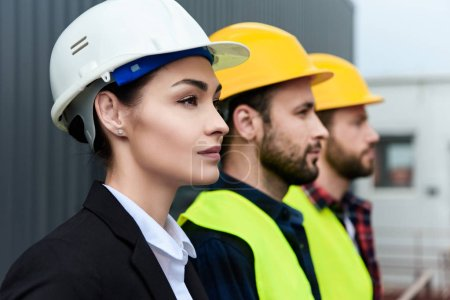 Photo pour Femme ingénieur et travailleurs masculins dans les casques sur la construction - image libre de droit
