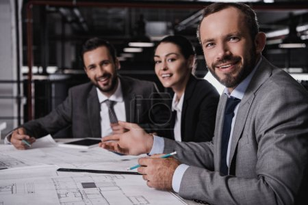 Photo for Male and female engineers in suits working with blueprints together - Royalty Free Image