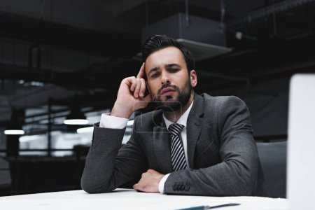 pensive male architect in suit working with blueprints