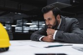 thoughtful male architect working in suit with blueprints