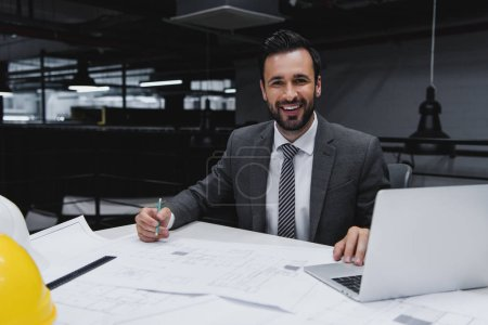 smiling male architect working with blueprints and laptop