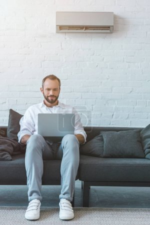 handsome bearded man using laptop on sofa, with air conditioner on wall behind