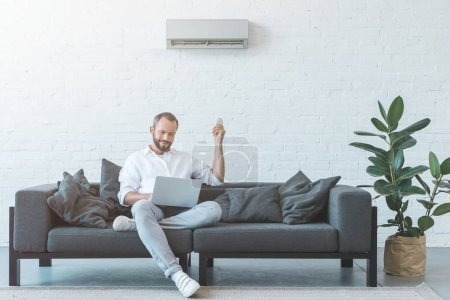 man turning on air conditioner with remote control while using laptop on sofa