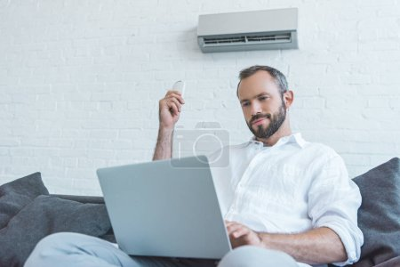 bearded man turning on air conditioner with remote control while using laptop
