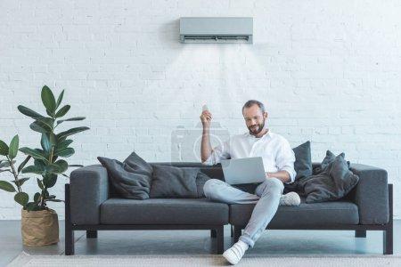 Photo pour Bel homme allumer le climatiseur avec commande à distance tout en utilisant l'ordinateur portable sur le sofa à la maison - image libre de droit