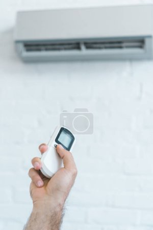 cropped view of man turning on air conditioner with remote control