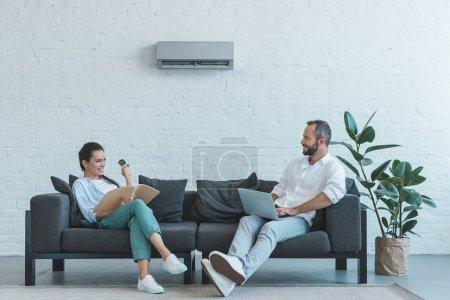 Photo pour Couple allumer climatiseur pendant la chaleur estivale tout en étant assis sur le canapé avec le livre et l'ordinateur portable - image libre de droit