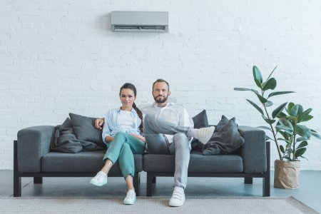 couple sitting on sofa during the summer heat at home with ficus and air conditioner on wall