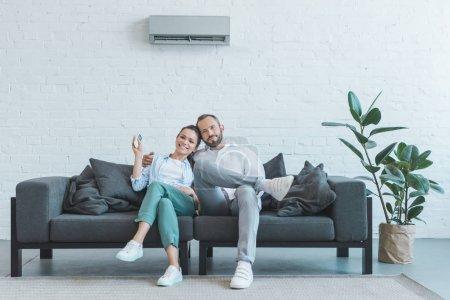 Photo pour Couple allumer le climatiseur pendant la chaleur de l'été à la maison - image libre de droit