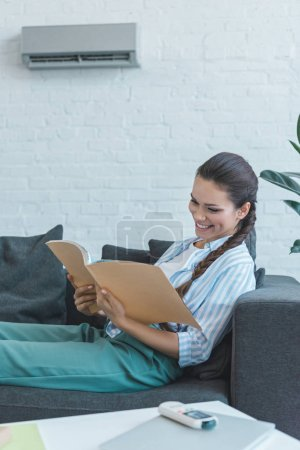happy woman reading book on sofa, with air conditioner on wall