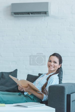 smiling woman with book sitting on sofa, with air conditioner on wall