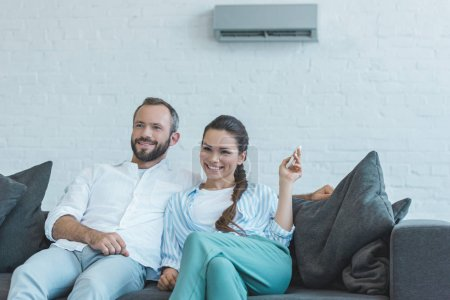 happy couple turning on air conditioner with remote control during the summer heat at home