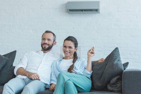 Photo pour Heureux couple allumer le climatiseur avec la télécommande pendant la chaleur de l'été à la maison - image libre de droit