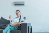 smiling woman turning on air conditioner with remote control while reading book on sofa