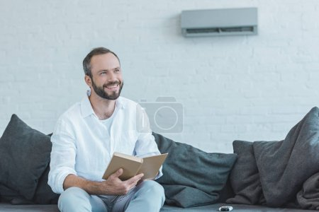 smiling bearded man with book sitting on sofa, with air conditioner on wall