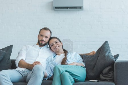 smiling couple sitting on sofa during the summer heat at home with air conditioner on wall