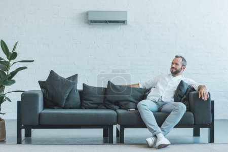 man sitting on grey sofa with remote control, air conditioner on wall