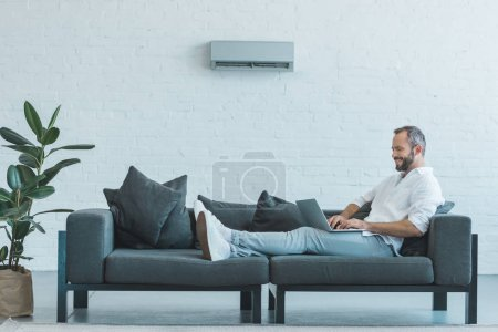 handsome man working with laptop on sofa, with air conditioner on wall at home