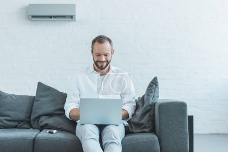 smiling man using laptop and sitting on sofa, with air conditioner on wall