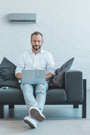 bearded man using laptop on sofa, with air conditioner on wall