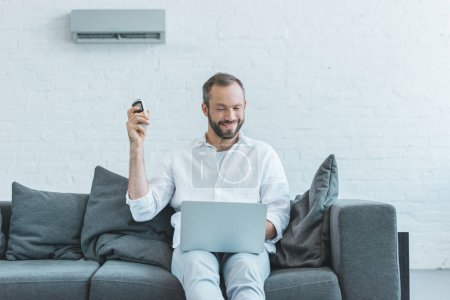 smiling man turning on air conditioner with remote control while using laptop