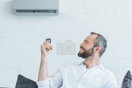 bearded man turning on air conditioner with remote control