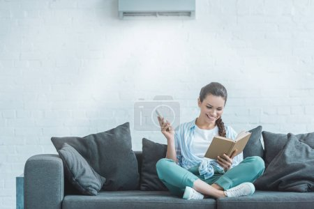 happy woman reading book while turning on air conditioner with remote control at home