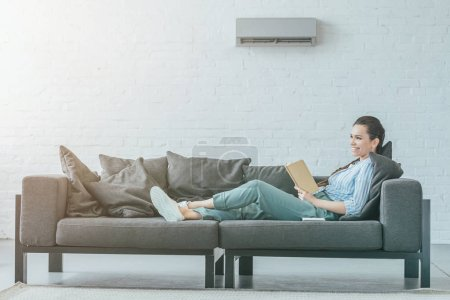 happy woman reading book on couch, air conditioner on wall, summer heat