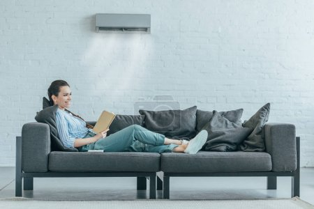 Photo pour Femme lisant livre sur canapé, climatiseur qui souffle sur lui - image libre de droit