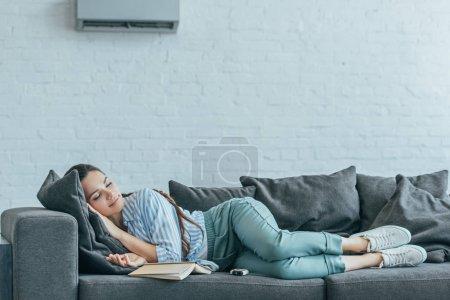 Photo pour Femme dormir sur canapé avec livre et climatiseur sur le mur - image libre de droit