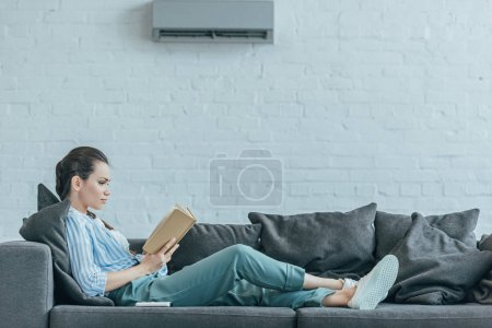 Photo for Woman reading book on sofa, with air conditioner on wall at home - Royalty Free Image
