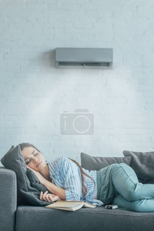 woman sleeping on couch with book and air conditioner blowing on her