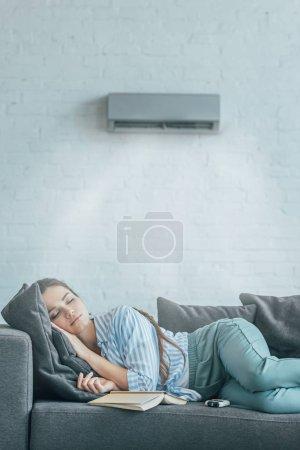 Photo pour Femme allongée sur canapé avec livre et air conditionné souffler sur elle - image libre de droit