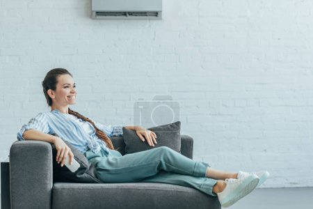 Photo pour Concept de chaleur d'été femme heureuse vous détendre sur le canapé avec le climatiseur sur un mur blanc, - image libre de droit