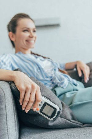 selective focus of woman sitting on sofa with air conditioner remote control