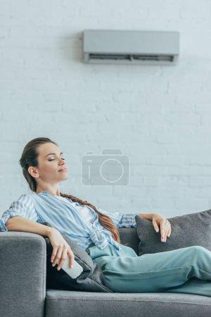 Photo pour Femme, reposant sur le canapé avec climatiseur sur mur, concept de chaleur de l'été - image libre de droit