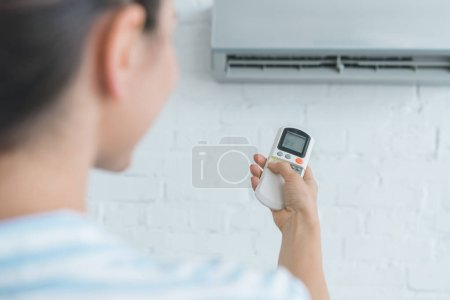 selective focus of woman with remote control  turning on air conditioner