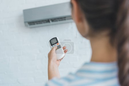selective focus of woman turning on air conditioner with remote control