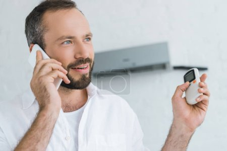bearded man talking on smartphone while turning on air conditioner with remote control