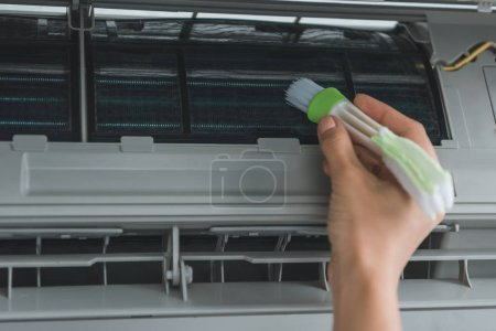 partial view of female worker cleaning air conditioner with brush