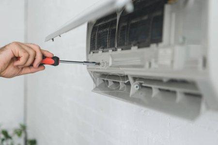 Photo pour Vue partielle du travailleur masculin réparation climatiseur avec tournevis - image libre de droit
