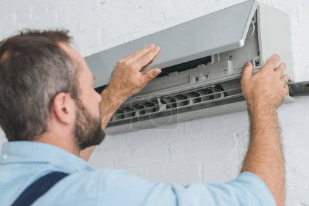 male worker fixing air conditioner at home