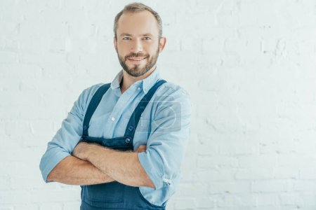 Photo for Smiling bearded worker in overalls posing with crossed arms - Royalty Free Image
