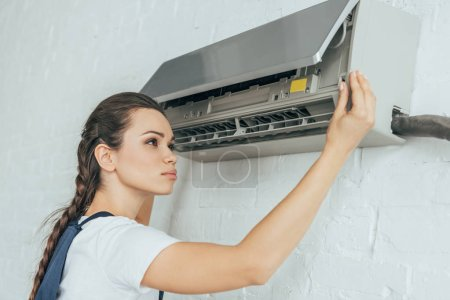 beautiful female worker repairing air conditioner