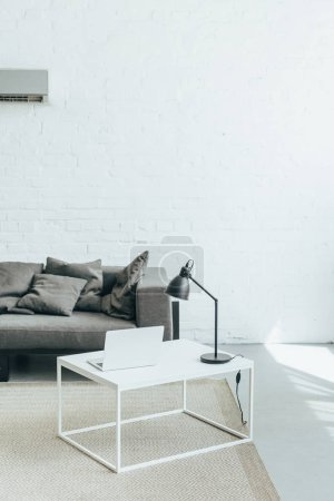 room with grey sofa, lamp and laptop on table and air conditioner on wall