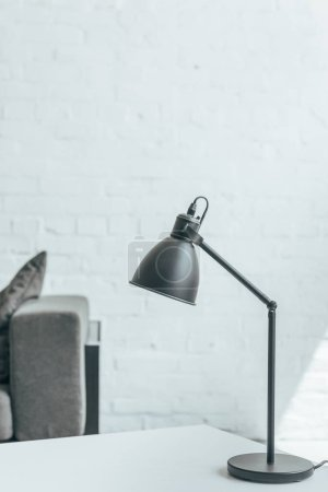 black lamp standing on table in room with grey sofa
