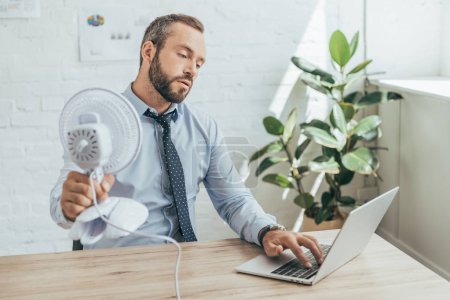 Photo for Businessman cooling himself with electric fan while using laptop in office - Royalty Free Image