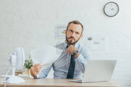 businessman with documents, laptop and electric fan in office