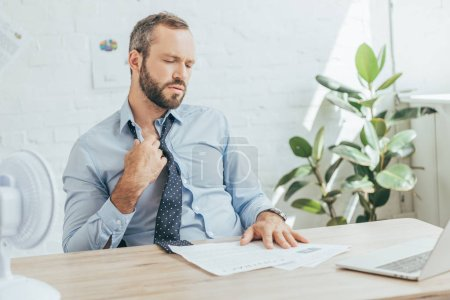 businessman conditioning air with electric fan in office with paperwork